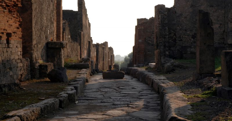 """""""Looking up a house-lined, stone-paved street of the ancient ruined Roman city of Pompeii."""""""